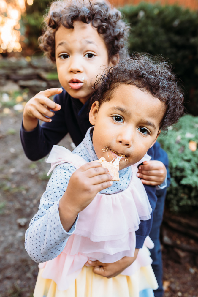 Brother is hugging his little sister from behind while they are both eating gooey s'mores at their Brooklyn family photo session.